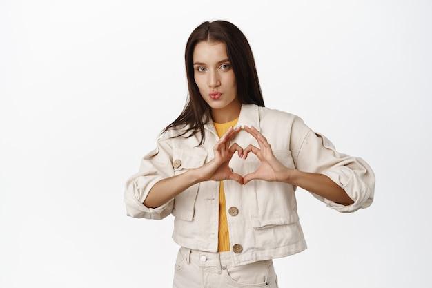Bella donna bruna pucker labbra che si baciano, mostrando il cuore ti amo segno, esprimi simpatia, racconta i suoi sentimenti, come smth, in piedi in giacca casual su bianco