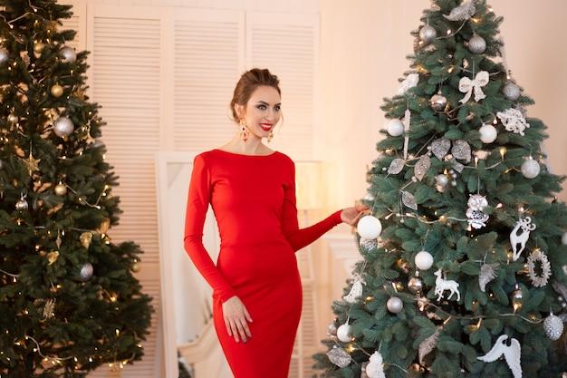 Bella donna castana in un vestito rosso si erge sullo sfondo di un albero di natale e tocca le decorazioni.