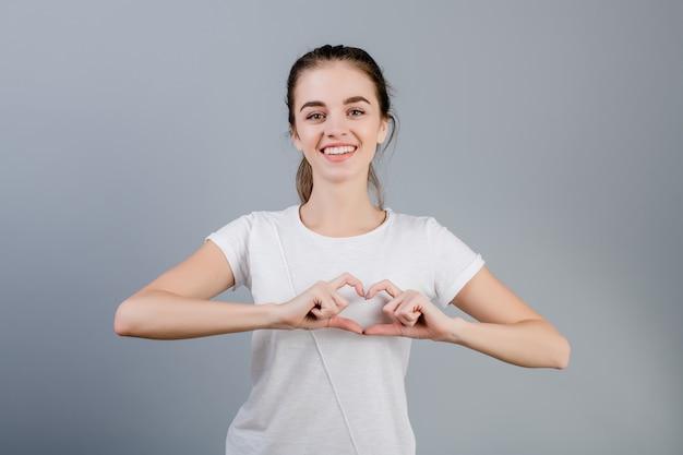Bella donna castana che mostra cuore con le mani isolate sopra grey