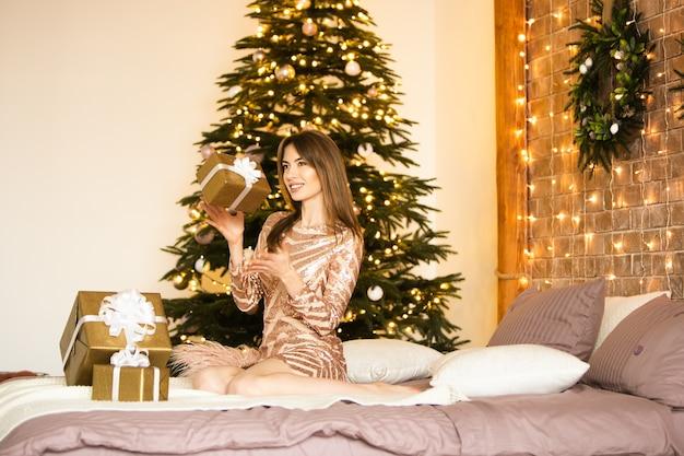 Una bella donna bruna si siede in un abito festivo sul letto, lancia e prende una confezione regalo, esulta e sorride. celebrazione di capodanno fatta in casa. focalizzazione morbida.