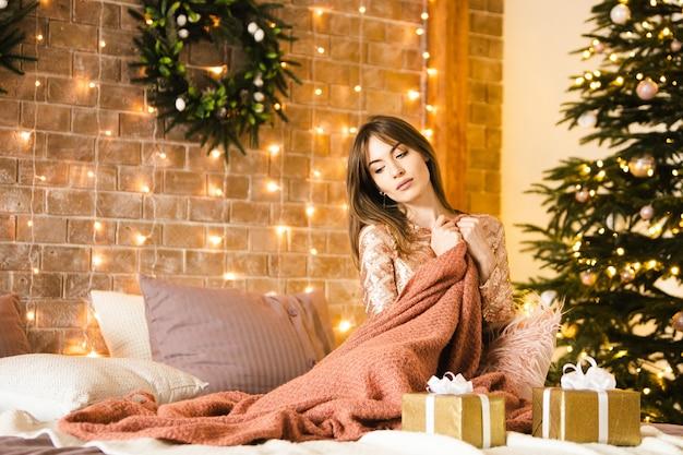 Una bella donna bruna si siede in un abito festivo sul letto