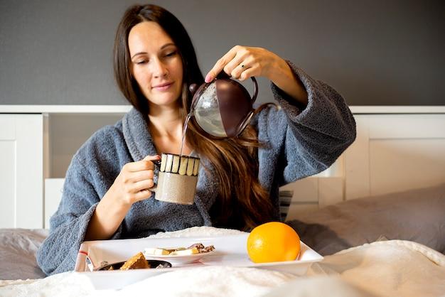 Bella donna castana che si siede sul letto, che tiene la tazza di tè e che fa colazione