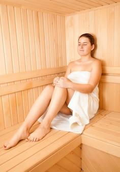 Bella donna castana che si siede sul banco alla sauna tradizionale di legno