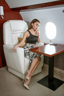 Bella donna castana che si siede in un sedile dell'aereo privato