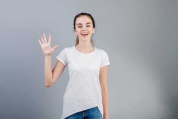 Bella donna castana che sorride e che conta le dita che mostrano cinque isolate sopra grey