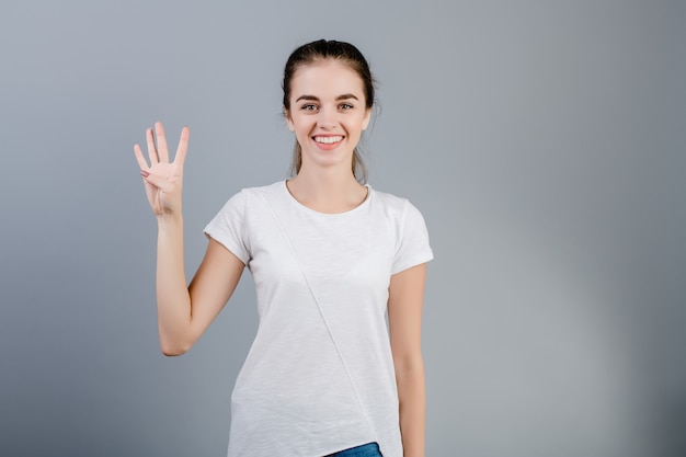 Bella donna castana che sorride e che conta le dita che mostrano quattro isolate sopra grey