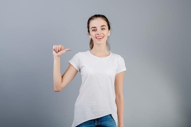 Bella donna castana che sorride e che conta le dita che mostrano una isolata sopra grey