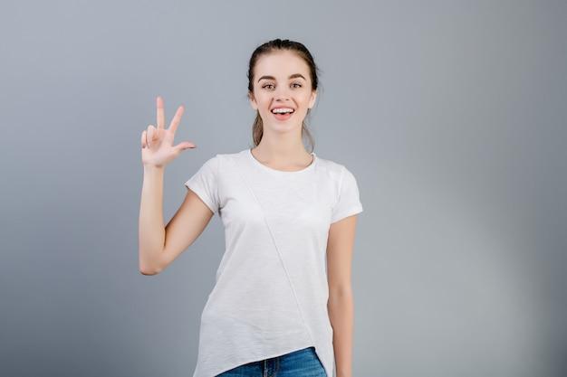 Bella donna castana che sorride e che conta le dita che mostrano tre isolate sopra grey