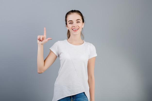 Bella donna castana che sorride e che conta le dita che mostrano due isolate sopra grey