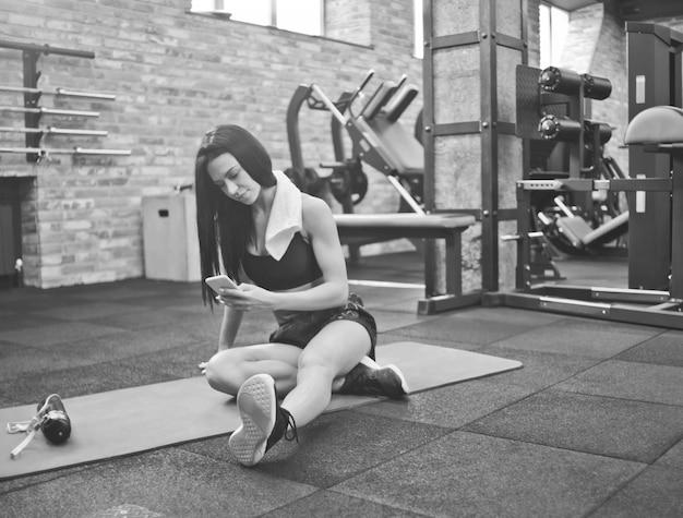 Bella donna castana in abiti sportivi con un asciugamano intorno al collo che si siede su una stuoia e usa lo smartphone in palestra. pausa di allenamento dopo un allenamento pesante
