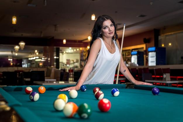 Bella donna bruna in piedi dietro il tavolo da biliardo
