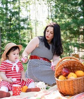 Bella donna castana in un vestito a strisce con il suo bambino