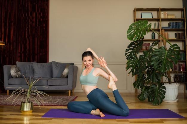 Bella donna castana in un top e leggings esegue pose di yoga sulla stuoia in una stanza a casa