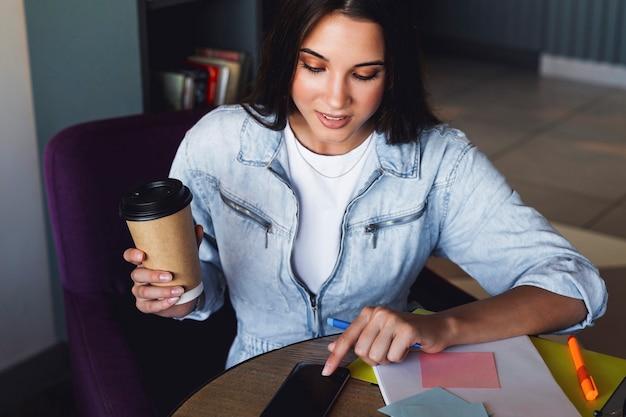 Bella donna castana utilizza gadget per il telelavoro dal caffè, tiene lo smartphone in mano. riqualificazione in linea