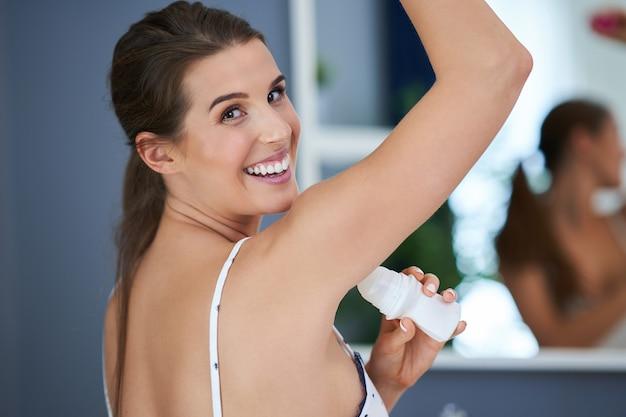 Bella donna bruna che usa il deodorante in bagno