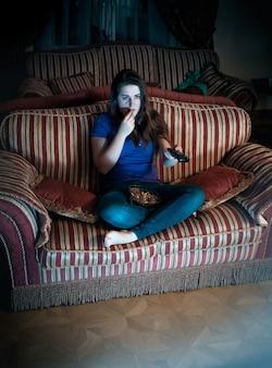 Bella donna bruna che guarda la tv di notte sul divano e mangia popcorn