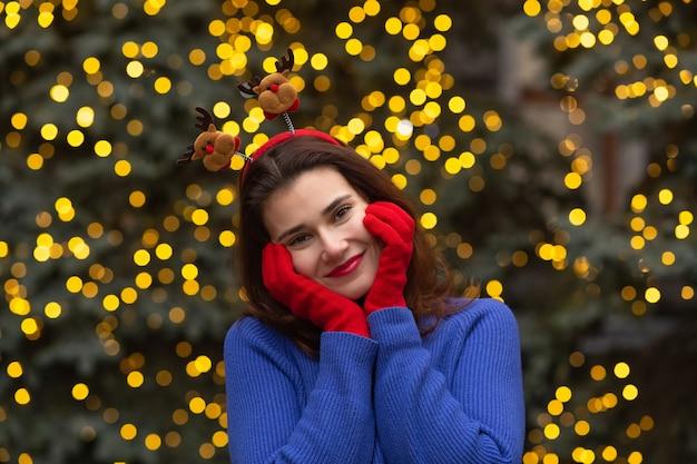 La bella donna castana indossa un divertente cerchio per capelli e guanti rossi che camminano alla fiera di natale nella piazza centrale della città