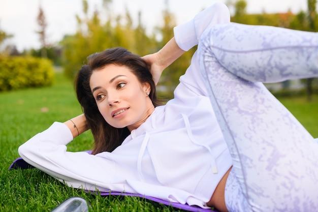 Bella donna bruna in abiti sportivi bianchi lat al tappeto su erba verde nel parco, facendo esercizio di fitness yoga con addominali scricchiolii