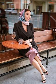 Bella donna castana con trucco luminoso in un caffè sulla strada con un bicchiere di vino