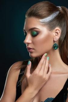 Bella donna castana con l'acconciatura con elementi di trucco lucido argento e verde