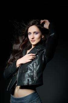 Bella donna castana con trucco naturale che posa su sfondo scuro. pelle del viso liscia e delicata