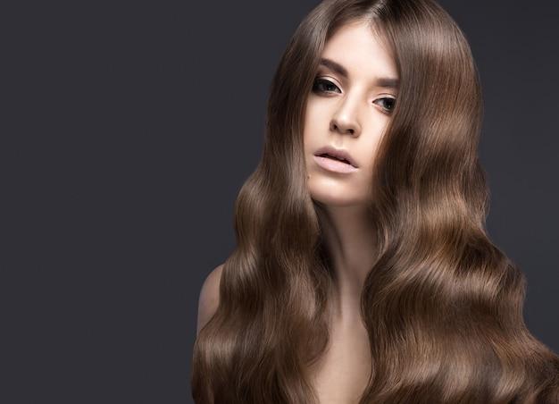 Bella donna bruna con i capelli perfettamente riccioli e trucco classico