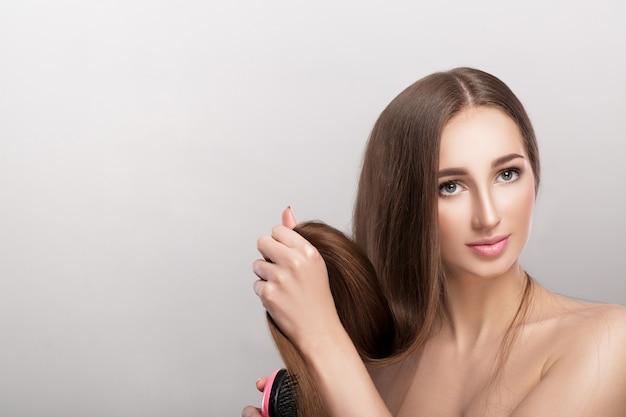 Bella donna castana con capelli lunghi lisci. cura dei capelli