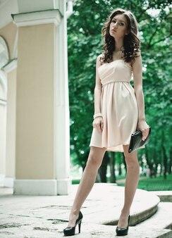 Bella bruna giovane donna che indossa abiti e cammina per strada, san pietroburgo, russia