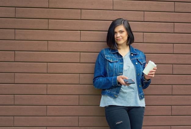 Bella giovane donna castana con tunnel nelle orecchie in una giacca di jeans blu con una tazza di caffè e smartphone in piedi davanti al muro di mattoni.