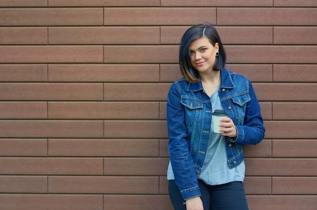 Bella giovane donna castana con tunnel nelle orecchie in una giacca di jeans blu con una tazza di caffè in piedi davanti al muro di mattoni.