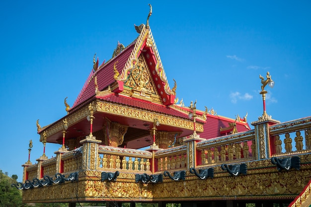 Una bellissima pagoda buddista con ornamenti e dettagli dorati. sul perimetro sono realizzate teste scure di elefanti. il tetto è rosso. cielo azzurro e limpido.