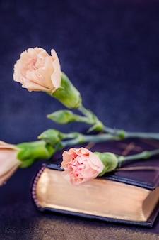 Bellissimi boccioli di fiori di garofano di colore rosa tea su un libro nero, copia dello spazio