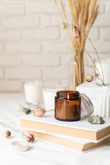 Belle candele accese con foglie di eucalipto e fiori secchi su una pila di libri bianchi