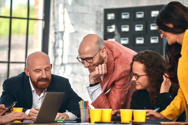 Bellissimi uomini d'affari usano gadget, parlano e sorridono durante la conferenza in ufficio. messa a fuoco selettiva