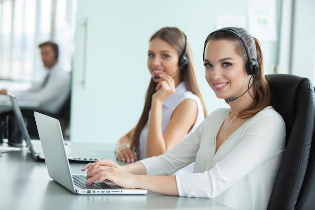 Bella gente di affari in cuffie utilizza i computer e sorride mentre lavora in ufficio