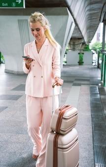 Bella donna d'affari all'aeroporto in partenza per un viaggio di lavoro. utilizzo dello smartphone per effettuare una telefonata