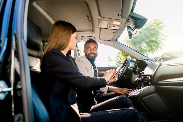 La bella donna di affari in vestito nero sta usando una compressa digitale e sta sorridendo mentre si sedeva nell'automobile insieme al suo socio in affari, uomo africano bello