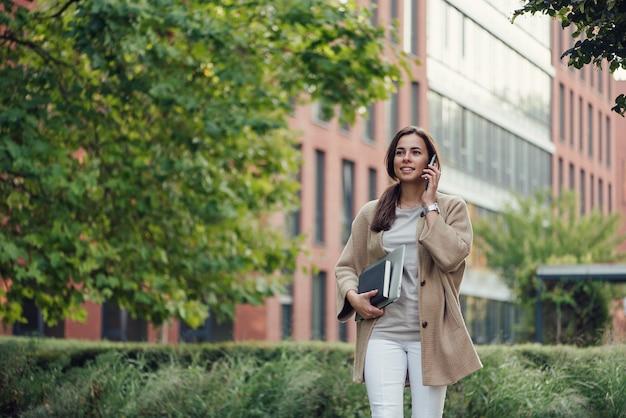 Una bella donna d'affari in abbigliamento casual con laptop e notebook all'aperto parla su smartphone