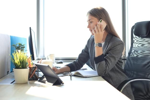 Bella donna d'affari sta parlando al telefono cellulare mentre è seduto in un ufficio moderno.
