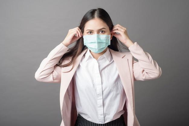 La bella donna di affari sta indossando la maschera chirurgica su fondo grigio