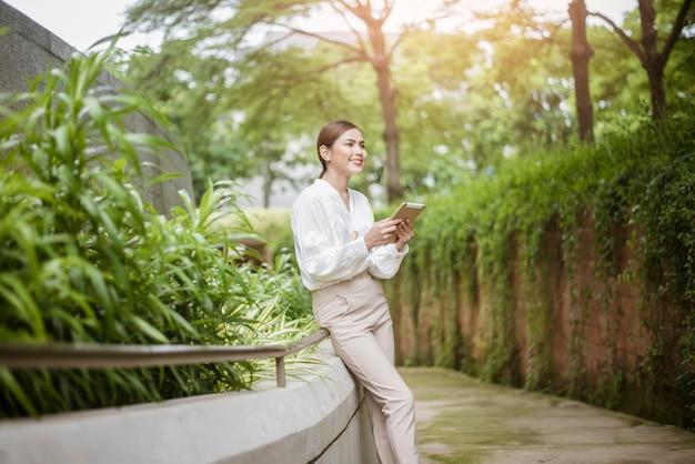 La bella donna di affari sta lavorando fuori dell'ufficio