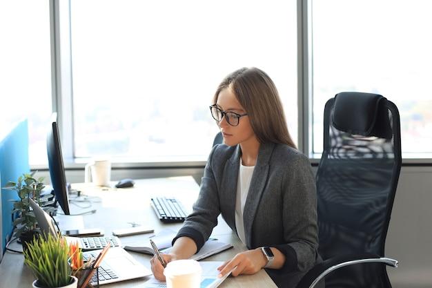 La bella donna d'affari sta scrivendo qualcosa mentre è seduta alla scrivania dell'ufficio.