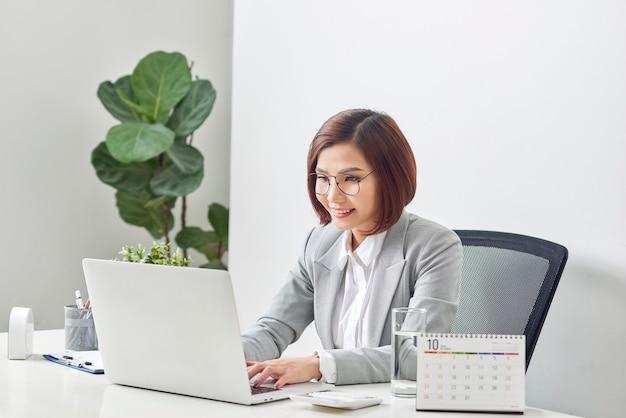 Bello sorriso della donna di affari che si siede allo scrittorio che lavora usando il computer portatile che guarda lo schermo che digita sul computer portatile sopra fondo bianco