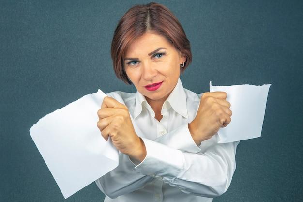 Bella donna d'affari strappando carta bianca a metà