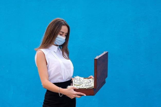 Bella donna d'affari che indossa una maschera medica a causa di un'infezione da coronavirus e tiene in mano dollari per la sua sicurezza
