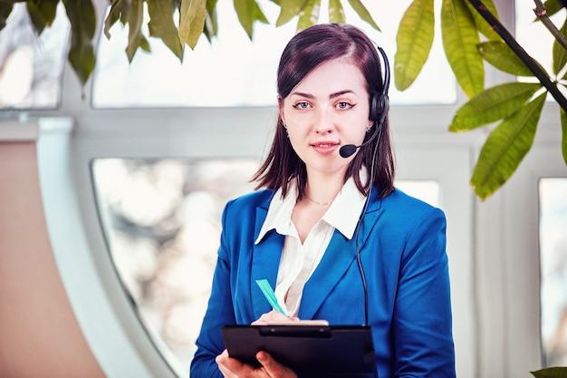 Bella donna d'affari che lavora alla sua scrivania con auricolare e laptop