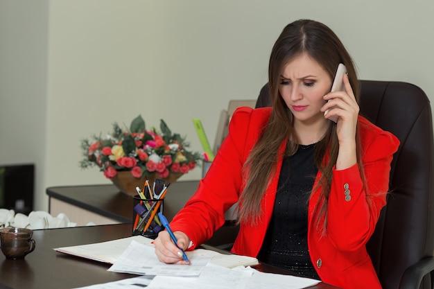 Bella donna d'affari che lavora alla sua scrivania con documenti e parla al telefono.