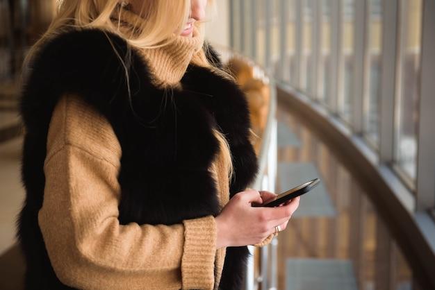 Bella donna d'affari scrivendo sms su un telefono cellulare