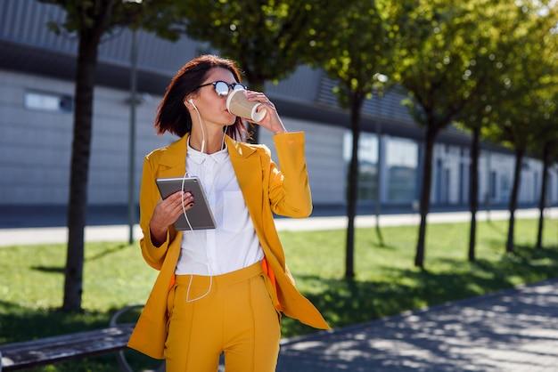 La bella donna di affari in vestito e gli occhiali da sole gialli con il computer e le cuffie della compressa beve il caffè mentre cammina sul vicolo.
