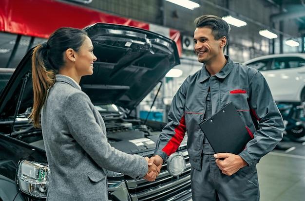 Bella donna di affari e meccanico di servizio automatico che agitano le mani. riparazione e manutenzione auto.